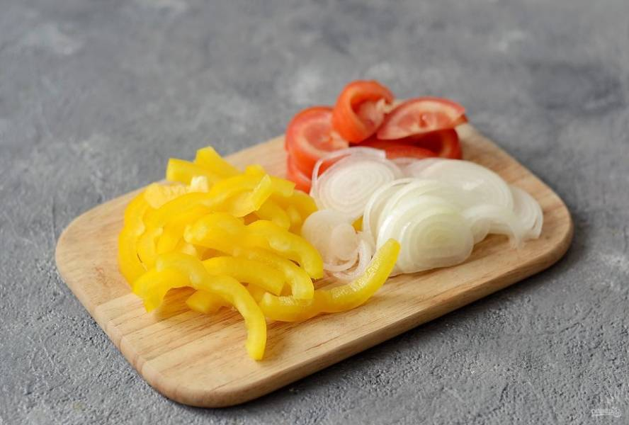 Репчатый лук нарежьте полукольцами. Болгарский перец очистите от семян и нарежьте соломкой. Помидоры нарежьте ломтиками среднего размера.