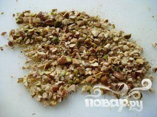 На противень положить миндаль, фисташки и  грецкий орех, поставить в духовку при 150 ° С, пока слегка не поджарятся. Вынуть из духовки, дать остыть и нарезать.