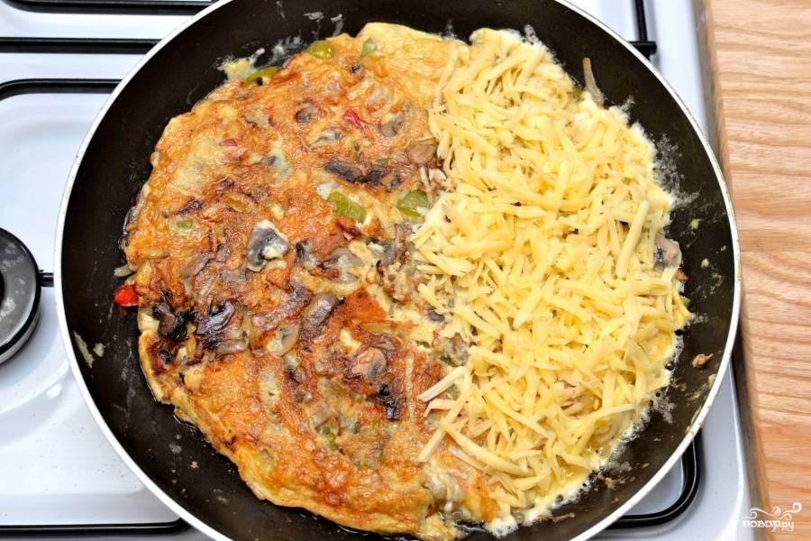 Визуально разделите омлет на две половинки и на одну сторону выложите тёртый сыр.