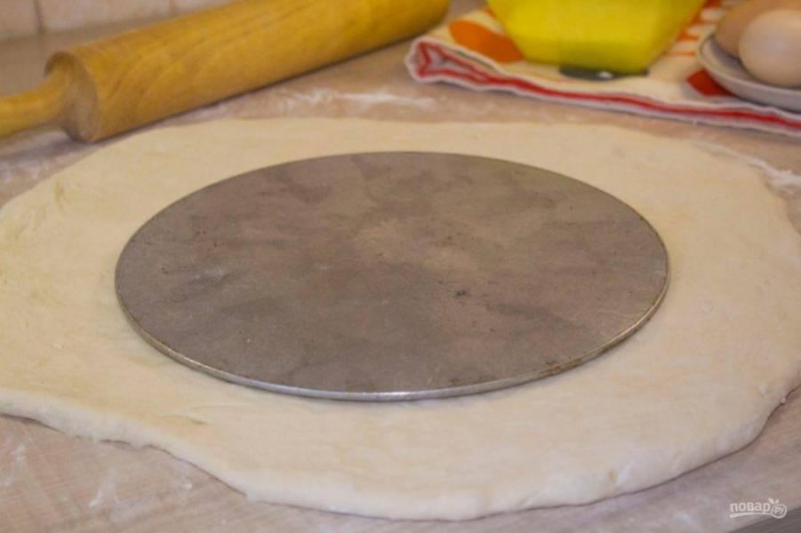 Раскатайте тесто в пласт. Края должны выступать за диаметр формы на 5-7 см.