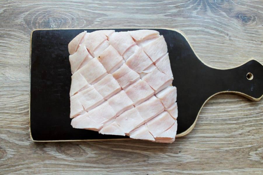 Свинину сполосните, и жесткой мочалкой хорошенько потрите кожу. Обсушите свинину бумажным полотенцем и сделайте разрезы со стороны кожи, прорезая только ее, не доходя до мяса.