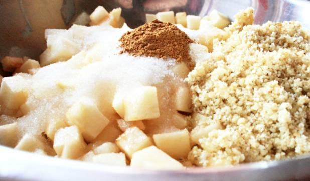 Добавляем к яблокам измельченные в блендере орехи, следом - ванилин, сахар, кукурузный крахмал и корицу. Всё это тщательно перемешиваем деревянной лопаточкой.