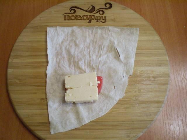 Лаваш порежьте на 4 части. На каждую часть кладем помидор, сыр, соль, перец.