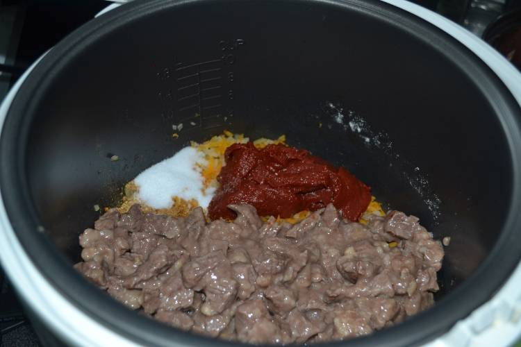 После того как режим закончится, перекладываем в чашу мясо, добавляем томатную пасту, солим все и приправляем специями.