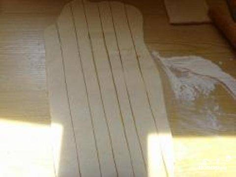 3.Слоеное бездрожжевое тесто немного разморозить. Раскатать его в пласт толщиной не более 0,5 см. нарезать тесто на тонкие полоски. Ширина полосок должна быть около 2 см.