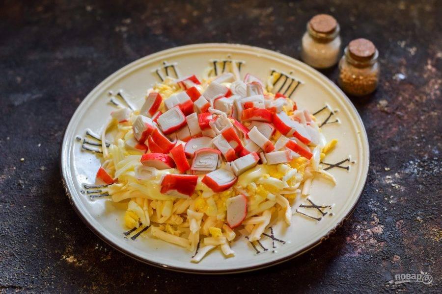 Крабовые палочки разморозьте, после нарежьте небольшими кусочками и выложите поверх яиц.
