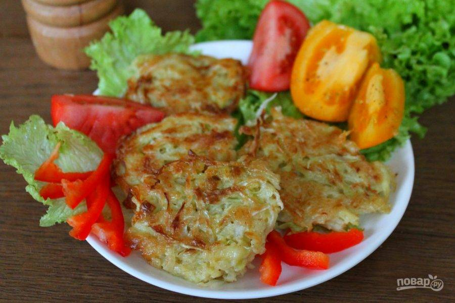 Оладьи из кабачков и капусты подаем горячими, вместе со свежими овощами и зеленью. По желанию, приправляем сметаной и чесноком. Приятного аппетита!