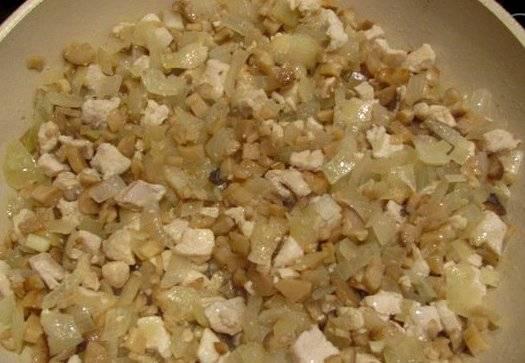 Далее мы нарезаем мелко куриное филе и обжариваем его до золотистого цвета на растительном масле. Затем добавляем к мясу измельченный репчатый лук и ножки шампиньонов, жарим все еще минут 5. Потом выкладываем на сковороду сметану, перемешиваем все и тушим начинку под крышкой несколько минут.