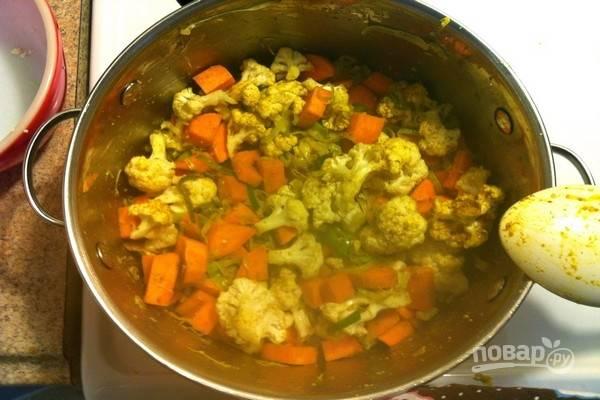 К луку-порею добавьте соцветия цветной капусты, батат, нарезанный кубиками, карри и зиру. Все перемешайте и готовьте 1 минуту.