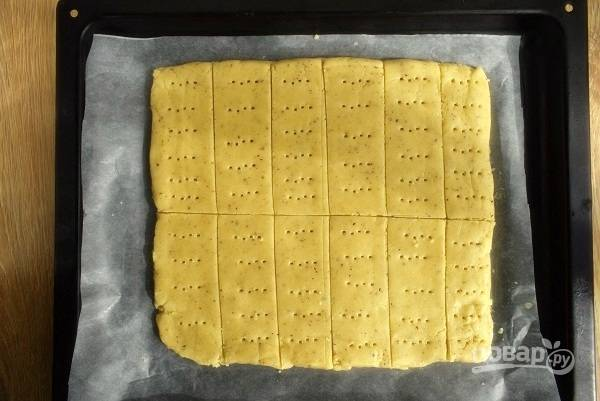На пергаменте разровняйте тесто в пласт размером примерно 20х25см. Нанесите ножом глубокие линии разреза, наметив 24 печенья. Но можно и больше, сделав печенье меньшим в размере. Наколите каждое вилкой в нескольких местах. Положите на противень.