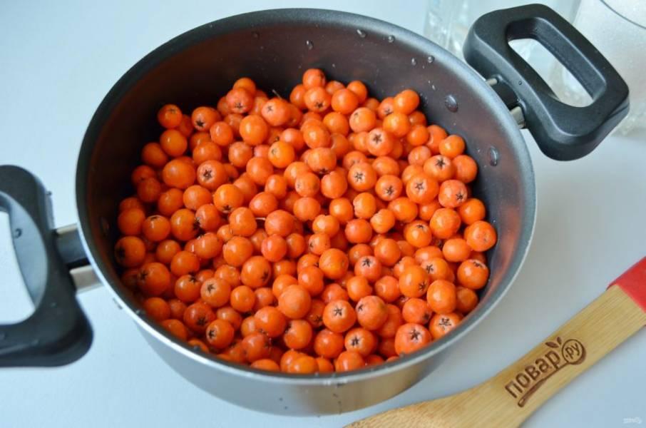 2. Ягоды рябины снимите с кистей и очень хорошо промойте в теплой воде, чтобы смыть всю пыль. Положите в антипригарную или эмалированную кастрюлю.