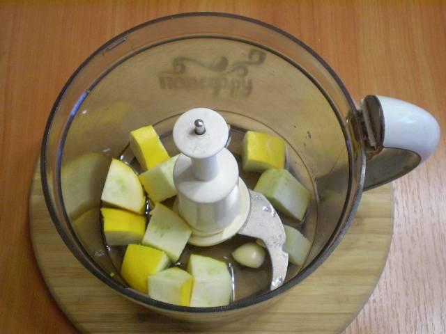 Кабачок должен быть молоденьким, старые или перезревшие плоды не подходят. Если кожура молоденькая и мягкая, снимать её не нужно. Просто порежьте кабачок на кусочки и положите в комбайн. Налейте воду, посолите, и добавьте зубчик чеснока. Отправьте пюрироваться.