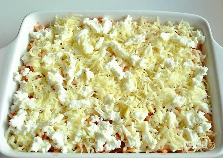 С макарон слейте воду и смешайте их с третью томатного соуса. В форму для запекания налейте пару ложек соуса и выложите часть макарон. Натрите пармезан, половину выложите на макароны вместе с половиной рикотты. Затем — вторая часть макарон, оставшийся соус, пермезан и рикотта. Сверху уложите мелко нарезанную моцареллу.