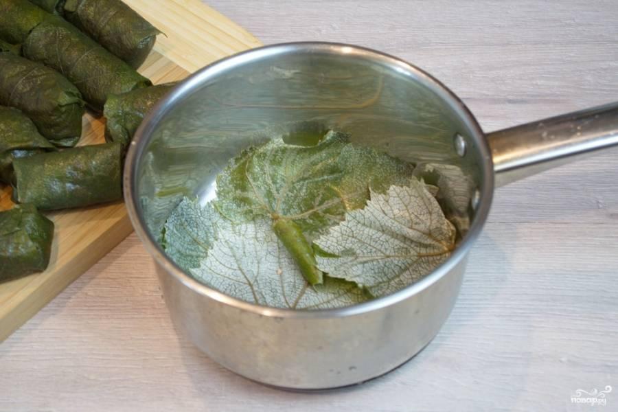 На дно толстостенной кастрюли выложите несколько листиков винограда. На них уложите долминки. Залейте бульоном. Поставьте на огонь и варите около 40 минут.