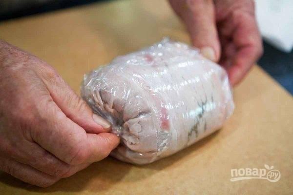 4. При помощи пищевой пленки сверните в рулет, после чего снимите пленку и выложите рулет на слоеное тесто.