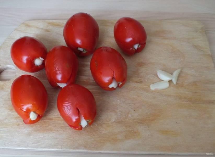 У помидоров, в месте плодоножки, сделайте глубокий крестообразный разрез. Зубчики чеснока почистите и разрежьте на 2-3 части. Возьмите разрезанную часть чеснока и воткните в разрез.
