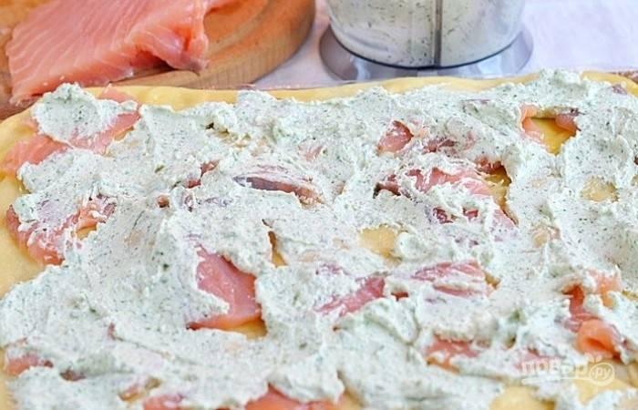 Расплавленный сыр растяните в тонкий прямоугольник. Сверху распределите начинку и кусочки тонко нарезанной сёмги.