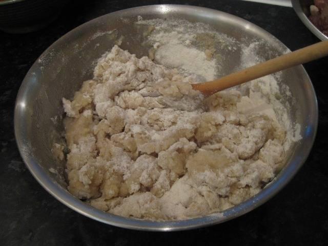 Просеиваем муку в миску, добавляем яйцо, перемешиваем. Затем вливаем горячие воду с жиром и перемешиваем сначала ложкой, а потом уже руками.