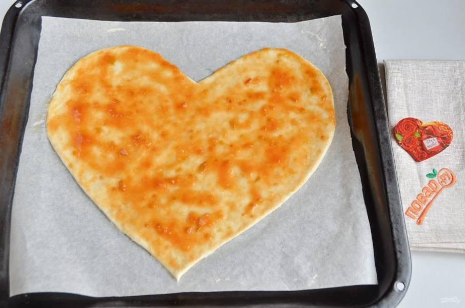 5. Переместите пергамент на противень. Смажьте пиццу соусом.