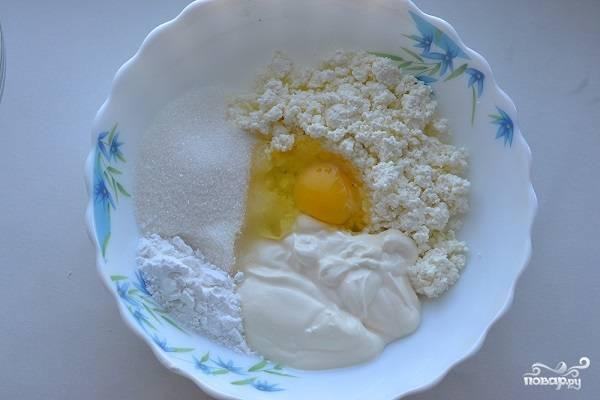 4. В глубокую мисочку отправьте протертый через сито творог, сметану и сахар. Вбейте яйцо и всыпьте немного крахмала. Теперь нужно взбить все венчиком до однородности.