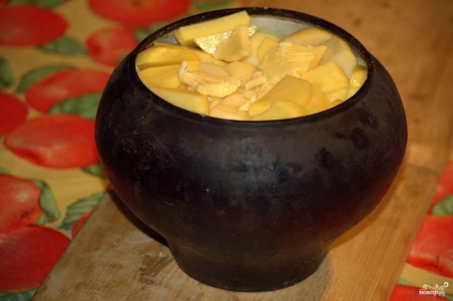 Затем выкладываем крупно порезанный лук и чеснок. Сверху — картошку и пару ложек топленого масла. Отправляем все в духовку, накрыв фольгой.