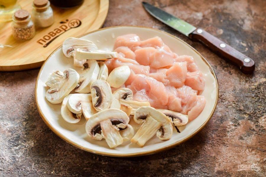 Ополосните и просушите куриное филе, шампиньоны лучше протереть кухонными влажными полотенцами. Нарежьте курицу кусочками, грибы нарежьте пластинами.