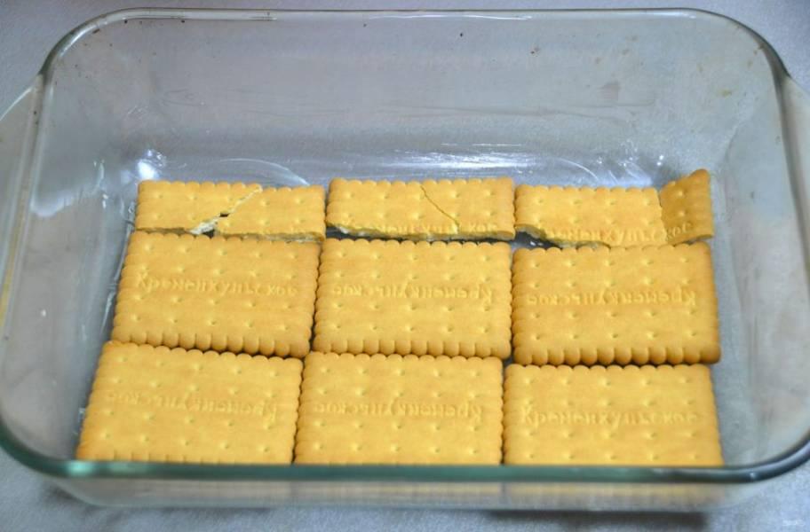 Смажьте форму сливочным маслом, на дно формы выложите печенье.