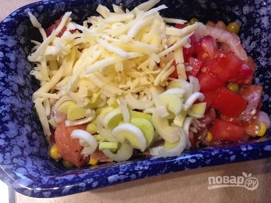 Выкладываем в форму для запекания рыбу с креветками и овощами, добавляем лук-порей, нарезанный кубиками помидор и половину натертого сыра. Перемешаем.