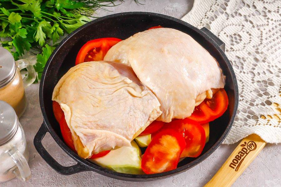 Промойте куриные бедрышки и выложите их на слой помидоров. Можно снять кожу, если хотите получить блюдо с минимальным содержанием жира.