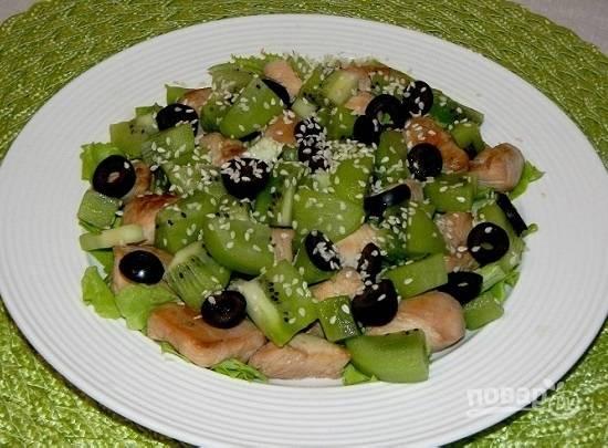 Выкладываем на салатные листья сначала кусочки курицы, а затем киви. Посыпаем маслинами и кунжутными семечками. Поливаем смесью оливкового масла и лимонного сока.