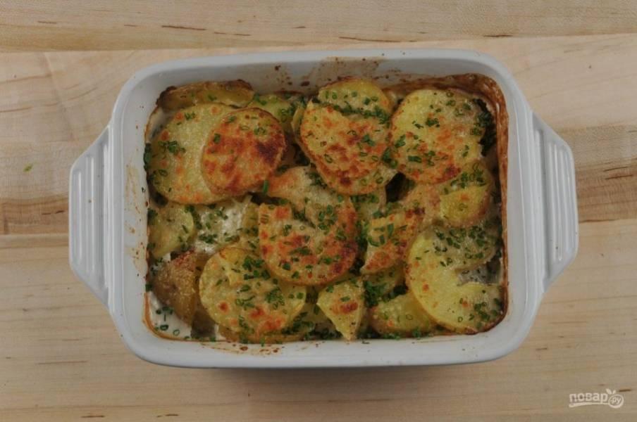 3. Пока курица запекается, подготовьте картофель. Перемешайте его с половиной лука-шалота. Добавьте сметану, соль, перец. Сверху натрите сыр. Отправьте картофель запекаться в духовку на 20 минут. Потом сверху всыпьте зелёный лук.