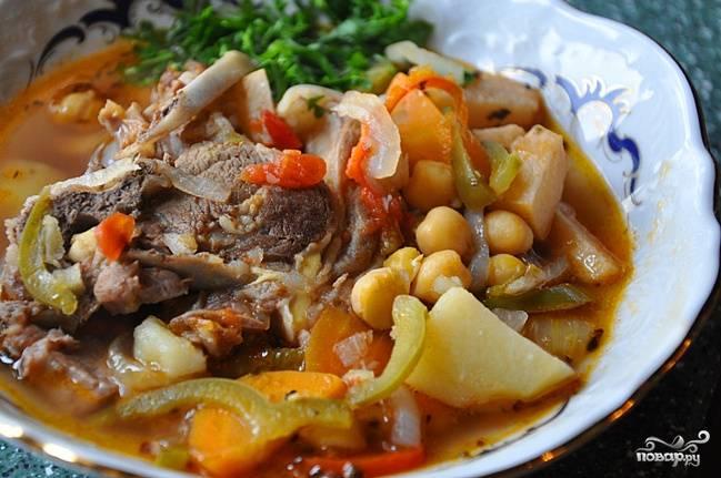 Добавить консервированный нут, сладкий и острый перец, помидоры, а также снятое с кости и измельченное мясо. Варить еще 5-7 минту, после чего огонь выключить, а супу дать отдохнуть под крышкой минут 15-20. Разлить по тарелкам, посыпать измельченной зеленью и чесноком. Суп из баранины  с картофелем готов!