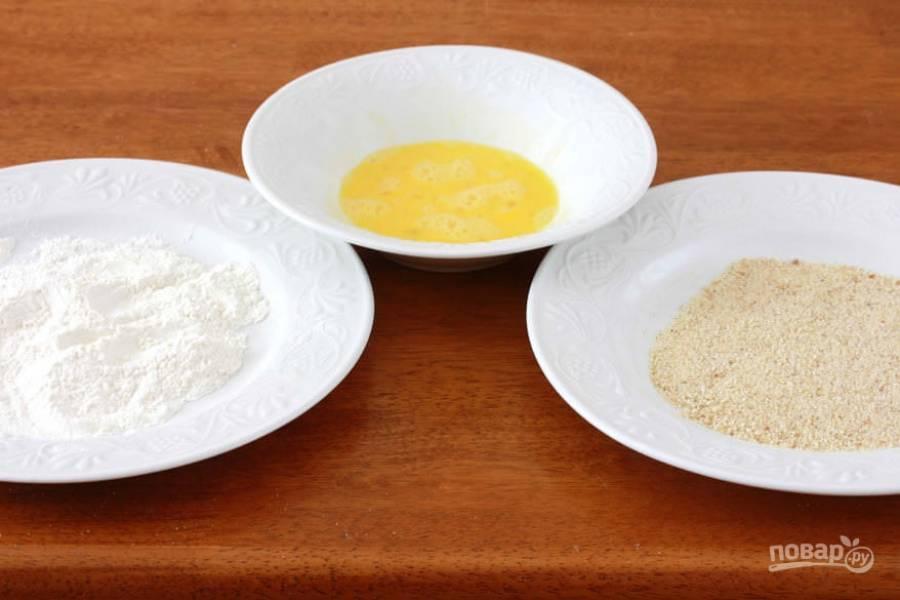 Приготовьте 3 отдельных миски для панировки: со взбитыми яйцами, сухарями и мукой.