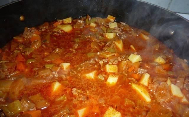 Теперь очередь картошки, добавляем ее к овощам и фаршу. Тушим под крышкой на небольшом огне до готовности картофеля.