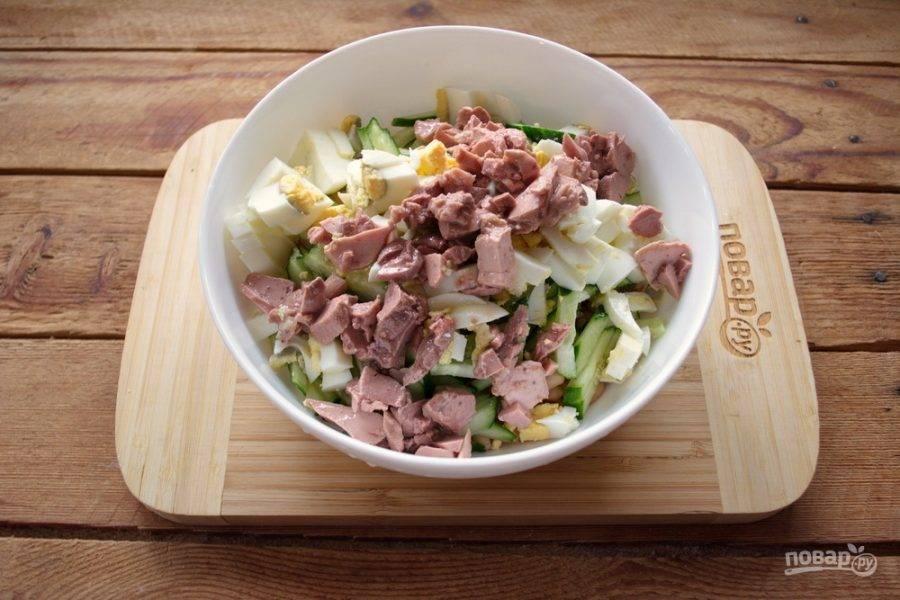 Печень трески извлеките из масла. Ножом нарежьте печень на небольшие кусочки, добавьте в салат.