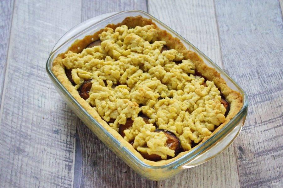 Выньте тесто из морозильника, натрите на крупной терке, разложите поверх слив. Поставьте пирог запекаться в духовку при 220°C на 20-30 минут до золотистого цвета.