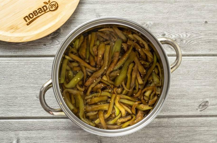 Добавьте баклажаны. Проварите их 10 минут в кипящем маринаде, затем откиньте на сито, чтобы стекла лишняя жидкость.