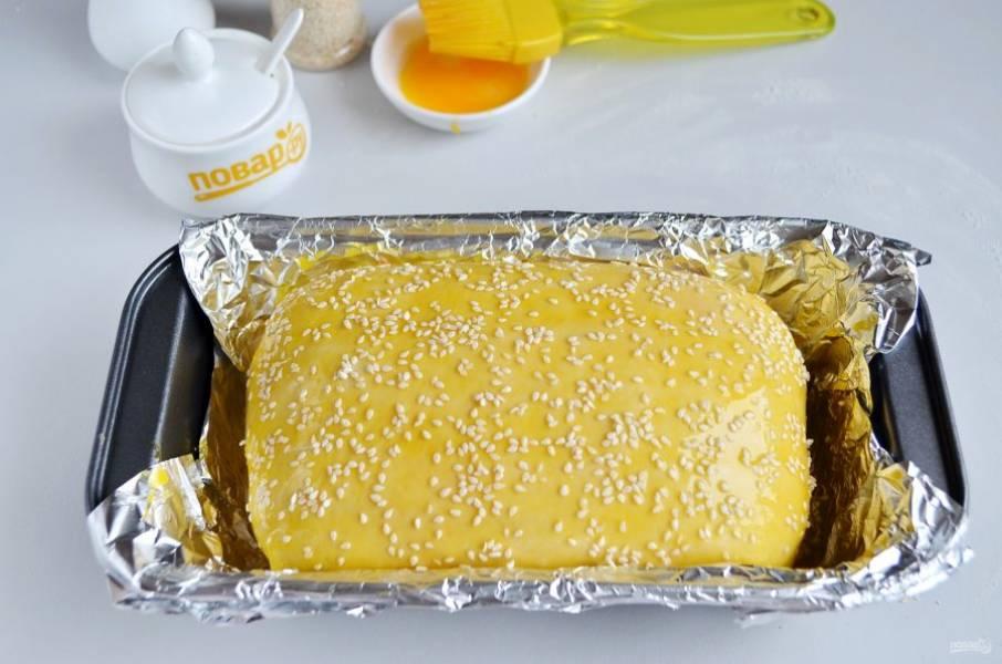 17. Форму для выпекания смажьте маслом или застелите фольгой, если сомневаетесь в своей форме. Положите хлеб швом вниз, смажьте желтком, посыпьте кунжутом и отправьте в теплую духовку для расстойки минут на 20 (если выпекаете на сухих дрожжах, тогда время расстойки увеличьте вдвое). После выпекайте при 180 градусах примерно 1 час.