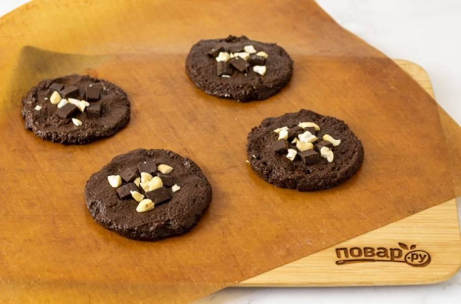 Сверху добавьте крупно порубленный шоколад и орехи. Вдавите их в тесто, чтобы закрепить. Выпекайте печенье 20-25 минут в заранее разогретой до 175 градусов. Затем полностью остудите на противне.
