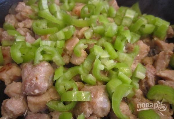 Нарежьте крупно промытый перец. Добавьте его в сковороду. Через 3 минуты перемешайте ингредиенты.