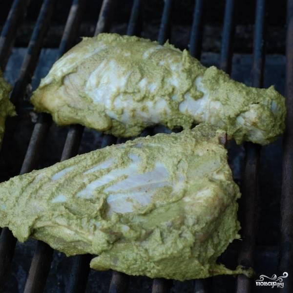 Выкладываем кусочки курицы вместе с осевшим на них маринадом на решетку гриля. Если готовите блюдо в домашних условиях - выкладывайте на противень.
