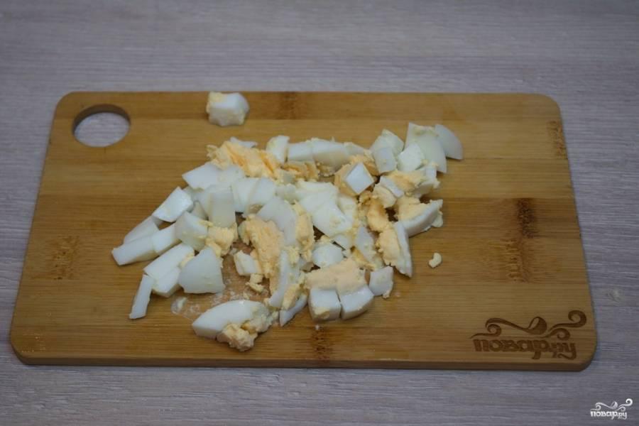 Отварные куриные яйца следует остудить, очистить и нарезать кубиками.