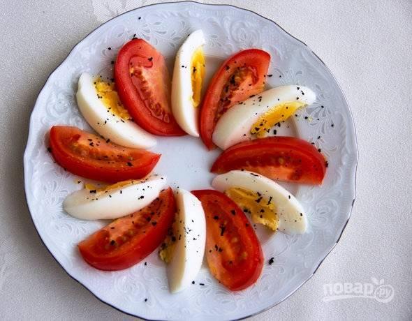 Поочерёдно выложите на тарелку яйца и помидоры. Посыпьте их базиликом. Можете сразу сделать порционные тарелки.