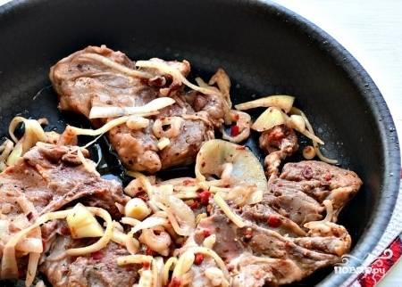 После этого разогрейте на сковороде масло, уложите в неё замаринованное мясо.