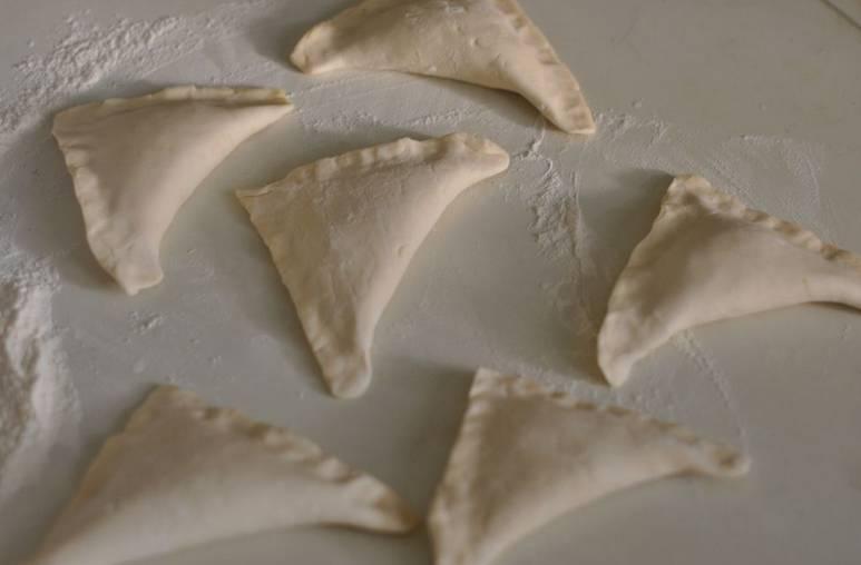 Формируем треугольные пирожки, края аккуратно защипываем. Чтобы пирожки не вздувались при выпечке, сделайте вилкой несколько проколов в тесте.
