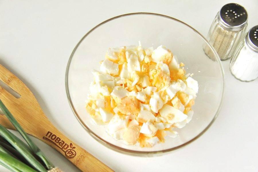 Вареные яйца очистите и нарежьте кубиками.