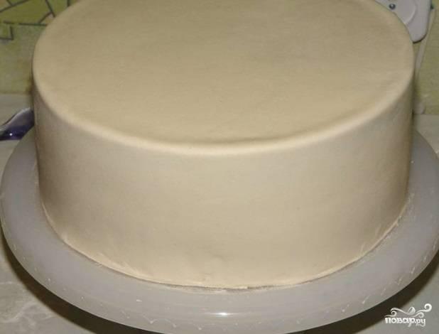 Теперь торт обтяните готовой сахарной пастой. Украсьте его по краям лентой.