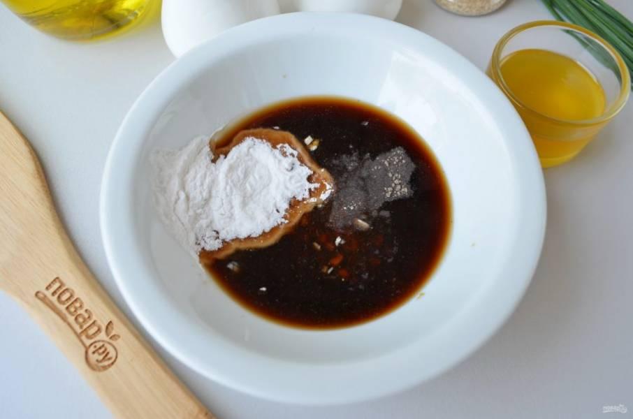 Смешайте в глубокой посудине: мед, соевый соус, рубленый чеснок, рисовый уксус, молотый имбирь, крахмал и черный перец молотый.