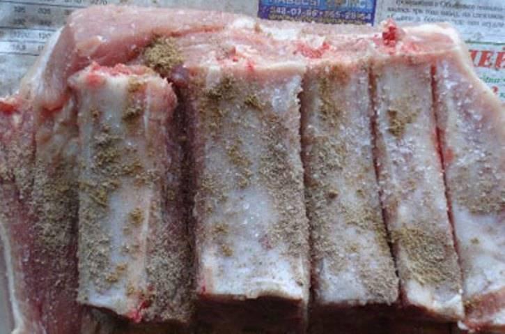 Ребрышки промойте, просушите бумажными салфетками. Натрите мясо крупной солью, перцем, приправой к мясу. Чеснок очистите, порубите и распределите равномерно по ребрышкам, добавьте лавровый лист.
