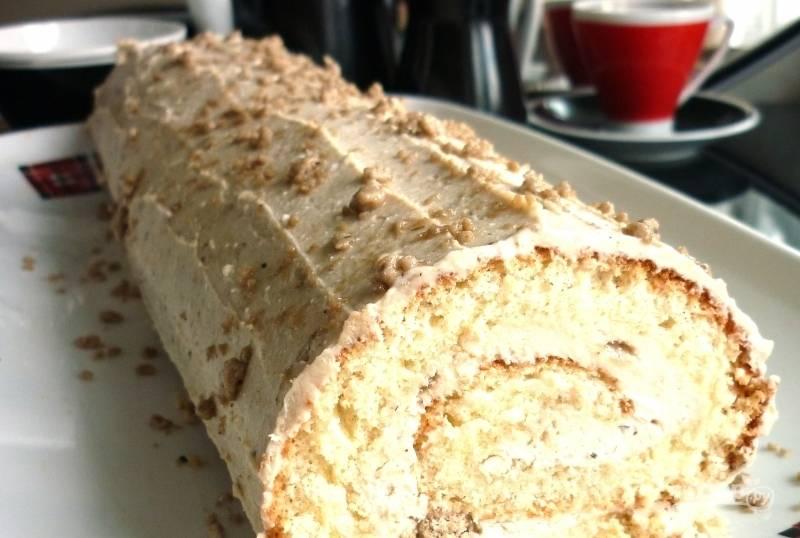 На остывший бисквит намажьте начинку. Сверните его плотно, прикрыв мокрым полотенцем на 5 минут. Затем сверху покройте рулет кремом и орехами. Приятного чаепития!